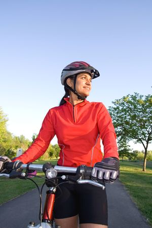 Close-up of woman standing next to bicycle and smiling in the park. Wearing sports gear and helmet. Vertically framed shot. photo