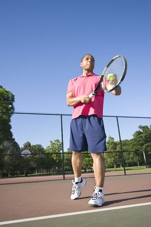vertically: A man is outside on a tennis court playing tennis.  He is about to serve the ball and is looking away from the camera.  Vertically framed shot.
