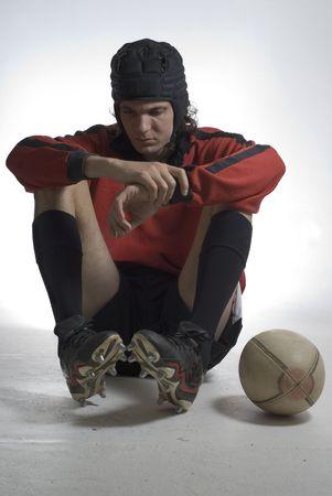El jugador de rugby sentado con sus codos sobre las rodillas buscando triste con su fútbol a su lado. Fotografía enmarcada verticalmente Foto de archivo - 3338740