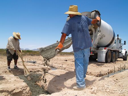 concrete: Two men are working on an excavation site.  They are guiding the cement into a trench.  They are looking down at their work.  Horizontally framed shot. Stock Photo