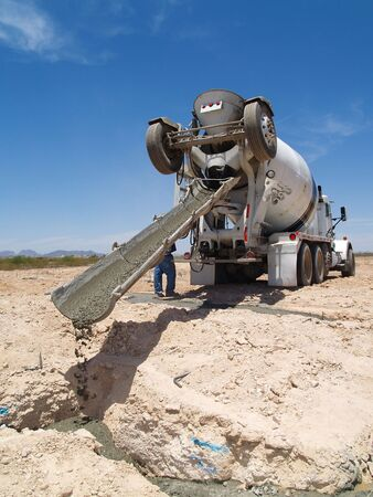 A cement truck is pouring cement into a foundation.  Vertically framed shot. Stock Photo