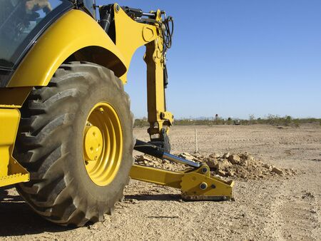 A giant steam shovel is digging into the dirt.  Horizontally framed shot. Stock Photo