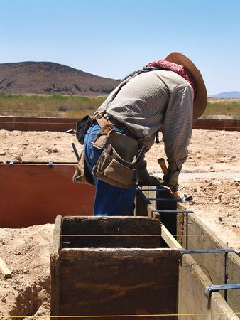 A construction worker is working on an excavation site.  He is looking down at his hammer.  Vertically framed shot. Stock Photo - 3339056
