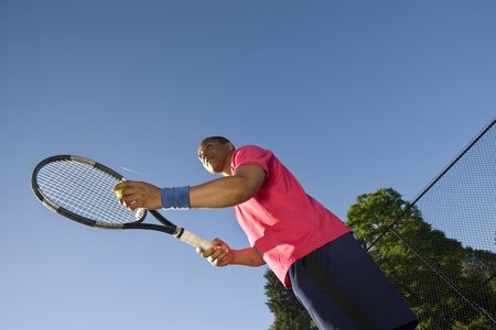 throw up: A man is outside on a tennis court playing tennis.  He is just about to throw the ball up to serve it and looking away from the camera.  Horizontally framed shot.