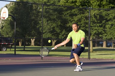 A man is outside on a tennis court playing tennis.  He is looking at the tennis ball.  Horizontally framed shot.