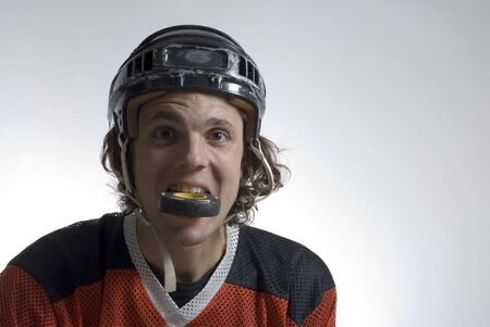 humor: Hockey player wearing a helmet jokes around with a hockey puck in his mouth. Horizontally framed photograph.