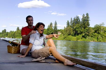 Happy couple laughing as they relax by the lake with a picnic basket next to them. Vertically framed photograph photo