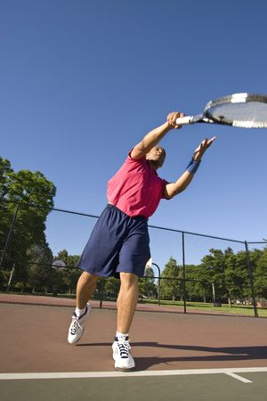 vertically: A man is outside on a tennis court playing tennis.  He had just served the ball and is looking at it in the air.  Vertically framed shot. Stock Photo