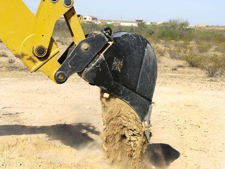 A giant steam shovel is releasing dirt onto the ground.  Horizontally framed shot.