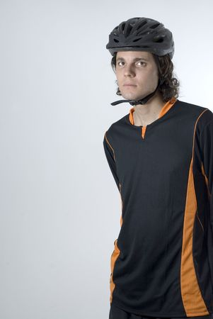 vertically: A man, standing, staring at the camera, wears a black and orange shirt with a black helmet. Vertically framed shot.