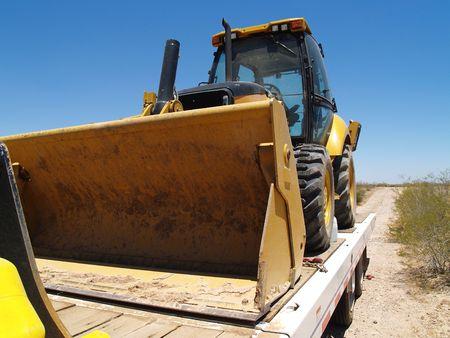 A work truck is hauling a steam shovel on a trailer.  Horizontally framed shot.