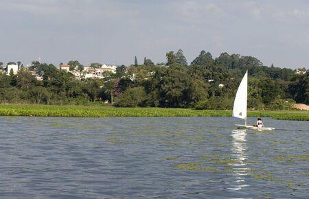 若いカップルは一緒に湖でセーリングします。 カメラから離れています。 水平方向にフレーム ショット。
