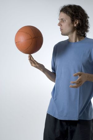 Man concentrates while balancing a basketball on his finger - Vertically framed photograph