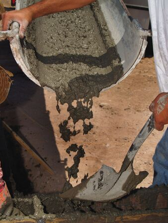 worksite: A man is working on an excavation site.  He is guiding wet concrete with a shovel.  Vertically framed shot. Stock Photo