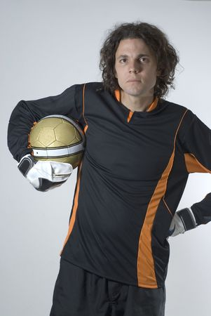 sternly: A man is in a studio posing with a soccer ball.  He is wearing a goalie uniform and looking at the camera sternly.  Vertically framed shot.