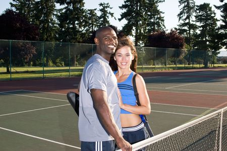 A young, active couple is standing on a tennis court.  They are wearing tennis clothes and smiling at the camera and hugging.  Horizontally framed photo. Stock Photo - 3364539