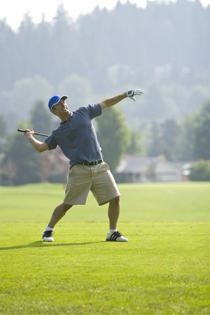 A young golfer, angry, preparing to throw his golf club. Vertically framed shot.