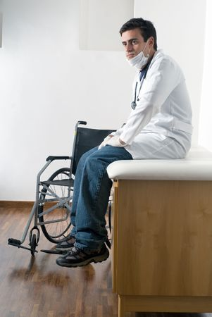 bore: A doctor is sitting on a bench in his office next to a wheelchair, and looking away from the camera.  Vertically framed shot. Stock Photo