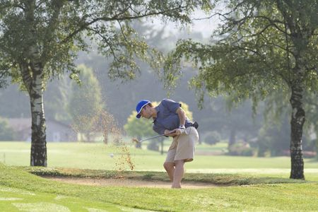 midlife: Man hitting golf ball out of sand trap - horizontally framed photo.