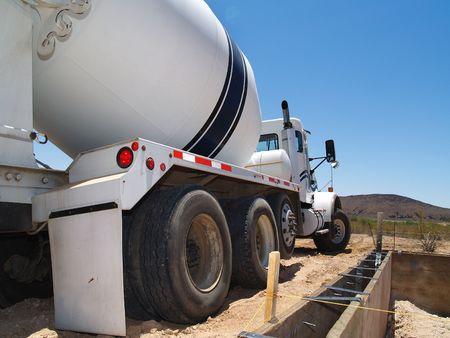 cemento: Un cami�n de cemento est� estacionado en exteriores en una zona des�rtica. Es al lado de un sitio de excavaci�n. Horizontal enmarcado disparo.