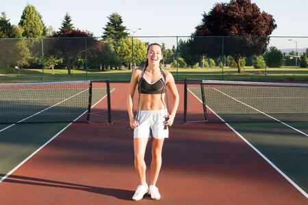 An attractive, fit woman is standing on a tennis court holding jump ropes around her neck.  She is smiling and looking at the camera.  Horizontally framed shot. photo