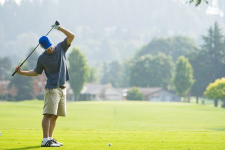 limber: A man is playing golf on a golf course.  He is holding his golf club over his shoulders and looking away from the camera.  Horizontally framed shot.