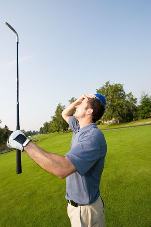 A man is grabbing his forehead in anger after missing a shot on a golfcourse.  He is holding a golf club and looking away from the camera.  Vertically framed shot.