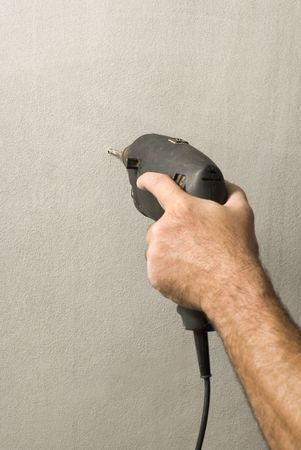 A hand, holding a power drill, drills a small hole through a wall. Vertically framed shot.