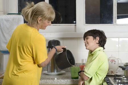 Woman and boy standing in kitchen. Woman pouring boy drink. Boy smiling at woman. Horizontally framed photo. Stock Photo - 3364675