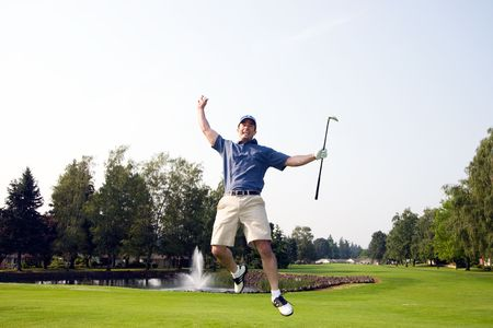 A man is jumping up and down on a golf course.  He is holding a golf club, smiling, and looking away from the camera.  Horizontally framed shot.