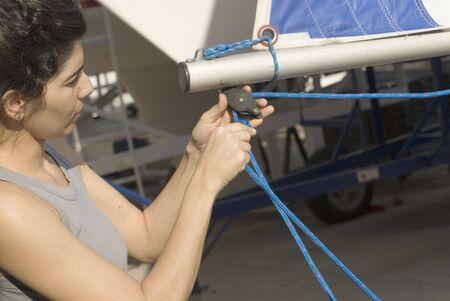 midlife: Woman setting sail rigging. Woman preparing to sail. Horizontally framed photo.