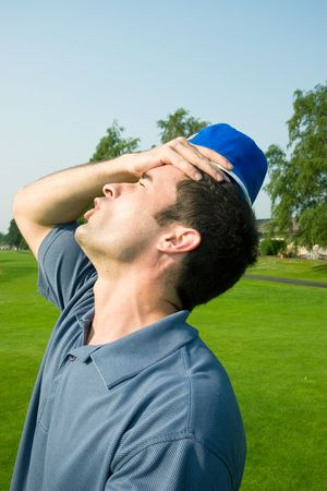 A man is grabbing his forehead in anger after missing a shot on a golfcourse.  He is looking away from the camera.  Vertically framed shot.