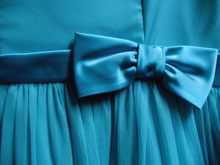 ruffle: A turquoise bow is tied onto a piece of fabric - Horizontally framed shot.