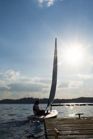 若いカップルは湖に浮かべてください。 彼らは、カメラから離れています。 ドラマを追加する意図的な太陽フレアを持つ垂直方向にフレーム ショットは。