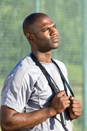 A young, attractive man is standing on the tennis court holding jump ropes around his neck.  He is staring off into the distance intensly.  Vertically framed shot.