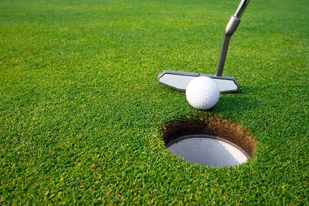 A man is standing on a a golf course.  He is putting the ball into the hole.  Vertically framed shot. Stock Photo