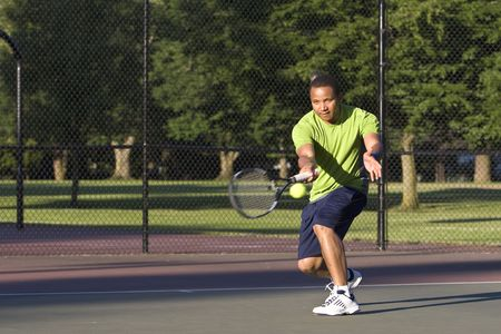 A man is outside on a tennis court playing tennis.  He is looking at the tennis ball, and about to hit it with his racket.  Horizontally framed shot.