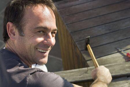 hammering: Man looking over his shoulder smiling at the camera while hammering. Horizontally framed shot.