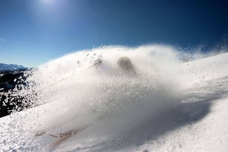 Skier carving a turn in a cloud of fresh powder. Horizontally framed shot. Stock Photo
