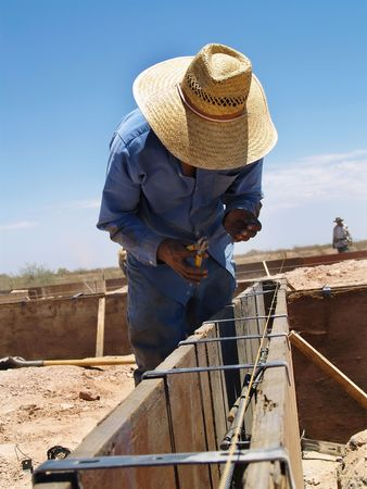 bending down: Un trabajador de la construcci�n est� trabajando en un sitio de excavaci�n. �l es la flexi�n hacia abajo y mirando a su trabajo. Vertical enmarcada disparo.