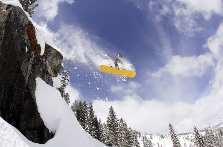 Snowboarder launching himself off a cliff in fresh powder. Horizontally framed shot.