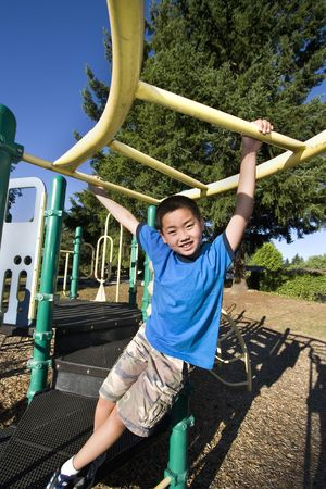 Young Asian boy climbing on jungle gym. He is smiling at camera. Vertically framed photo. Stock Photo
