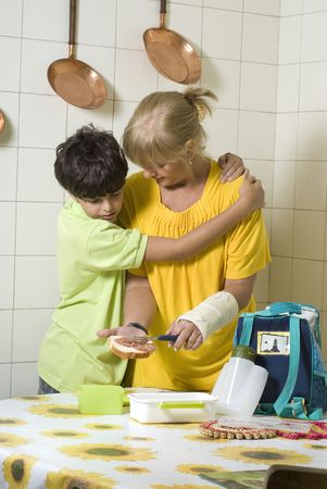 making a sandwich: A woman is making a sandwich for her son.  He is hugging her.  She is looking at him and he is looking at the sandwich.  Vertically framed shot. Stock Photo