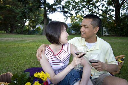 結婚されていたカップルは公園で一緒に座っています。 ワイングラスを持って、ピクニック毛布の上に座っています。 彼らは笑みを浮かべて、互いを見るします。 水平方向にフレーム ショット。