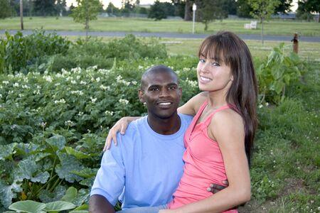 男性と女性が庭で一緒に座っています。女性は男性の膝の上に座っています。彼らは微笑し、カメラを見てします。水平方向にフレームのショット。