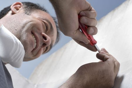 A man, wearing a mask around his neck, uses a screwdriver to put a screw into a wall. Horizontally framed shot. Stock Photo
