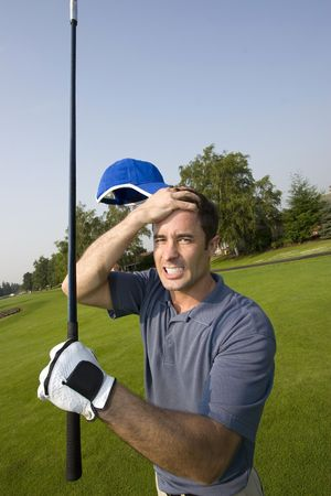 A man is grabbing his forehead in anger after missing a shot on a golfcourse.  He is holding a golf club and looking the camera.  Vertically framed shot.