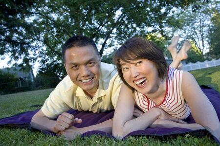 結婚されていたカップルは一緒にピクニック毛布で公園で横たわっています。女性は笑っています。彼らは微笑し、カメラを見てします。水平方向にフレームのショット。