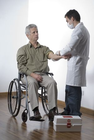 A patient is sitting in a wheelchair at a doctors office.  The doctor is bandaging his arm.  The doctor is looking at the patient and the patient is at the doctor.  Vertically framed shot.