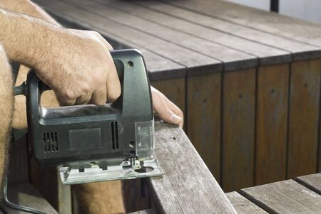 resale: Hand holding jigsaw sawing board. Horizontally framed shot.